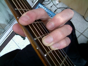 photo of E shape minor barre chord from guitarist's POV