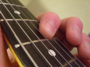 photo showing the index finger rolled back on to the B string