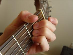 muting the low E string using the fret hand thumb