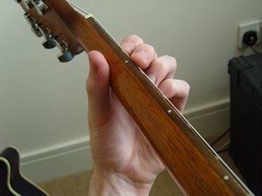 holding the guitar neck - top view