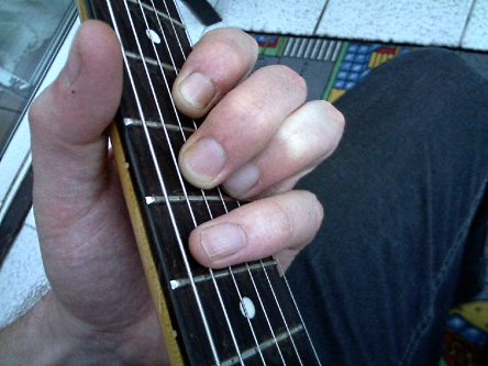 muting the 5th string using pinky finger