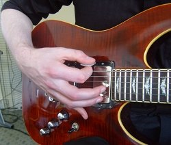 pinky finger rested on guitar body near pickup switch