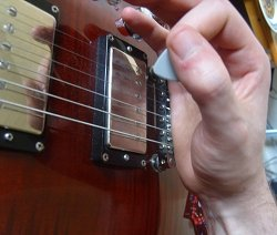 photo of fret hand rested on guitar bridge