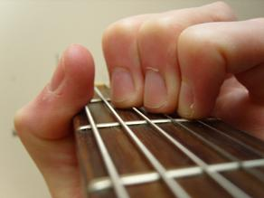 close up of thumb muting the E string