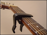 clamp style guitar capo attached to neck