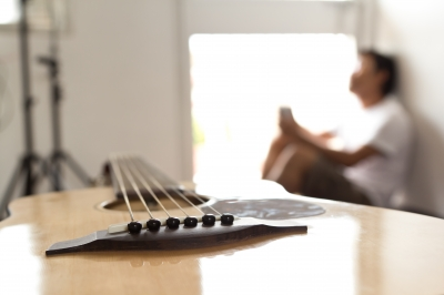 Man sitting away from his guitar