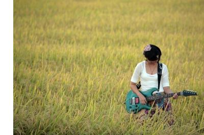 girl playing guitar in field