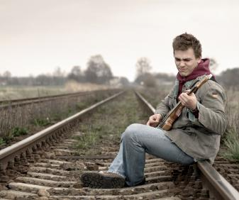 man sat on railway track playing guitar