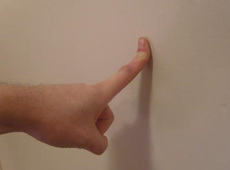 index finger stretched against a wall