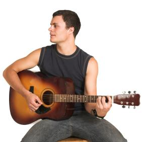 man sat down holding an acoustic guitar